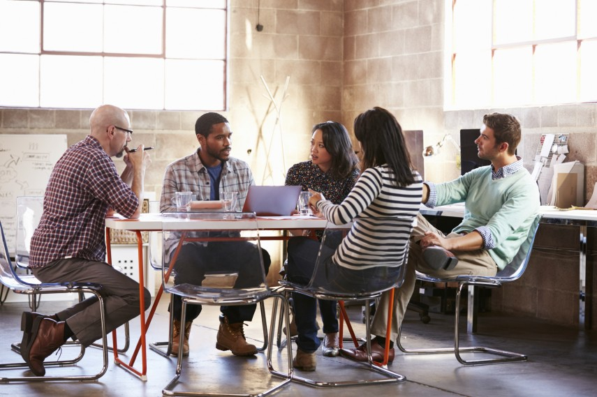 Group Of Designers Having Meeting Around Table In Office